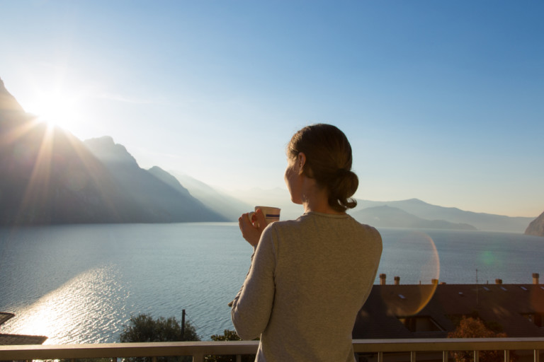 woman enjoying coffee on a seaside balcony
