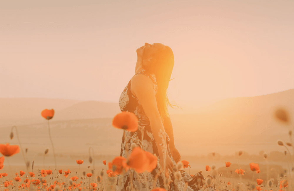 woman in a flower field during sunrise